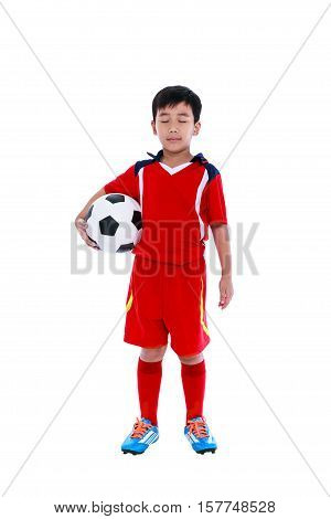 Full length of young asian soccer player in red uniform holding his soccer ball. Child standing with closed eyes for concentrate before the competition studio shot. Isolated on white background.