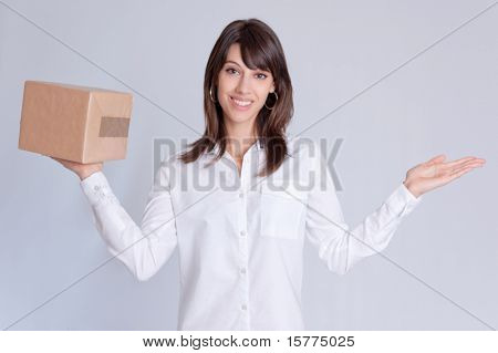 Young woman with a balance position a parcel in one hand and the other one empty