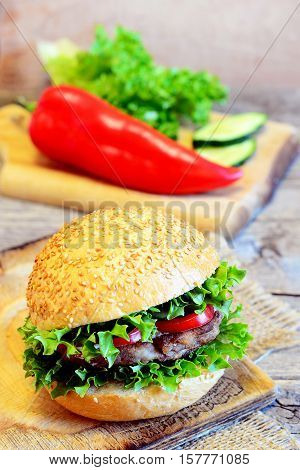 Sandwich with a bean cutlet, lettuce, red pepper and cucumber. Hearty sandwich on a wooden board, fresh vegetables. Simple vegetarian breakfast sandwich idea. Vintage style. Closeup