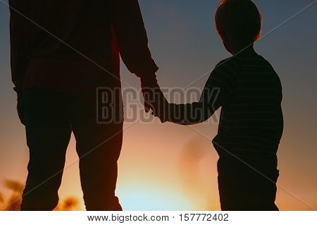 silhouette of father and son holding hands at sunset sky