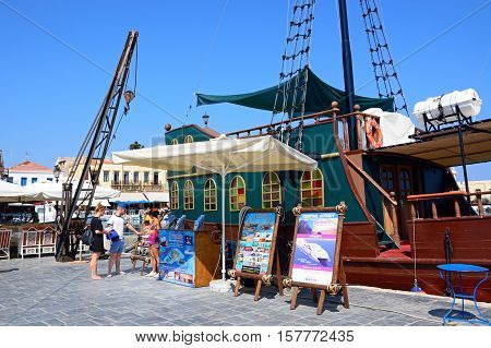 RETHYMNO, CRETE - SEPTEMBER 15, 2016 - Tourists looking at signs by a Galleon ship in the inner harbour with waterfront restaurants to the rear Rethymno Crete Greece Europe, September 15, 2016.