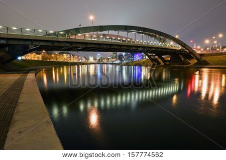 VILNIUS LITHUANIA - November 21: Mindaugas Bridge at night on November 21 2016 in Vilnius Lithuania. It crosses Neris River and connects Zirmunai elderate with the Old Town of Vilnius.
