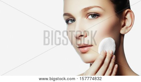Beautiful brunette woman removing makeup from her face skin care concept. Beauty fresh girl cleaning face with cotton swab. Beautiful young woman cleaning her face with cotton