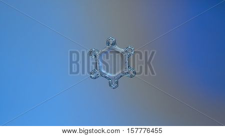 Snowflake on bright blue - gray gradient background, horizontal version. This is macro photo of real snow crystal: small plate with simple shape and big central hexagon with unusual pattern of dots.