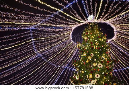 Fairy Christmas tree decorated with bright garlands and baubles on x-mas eve at Moscow