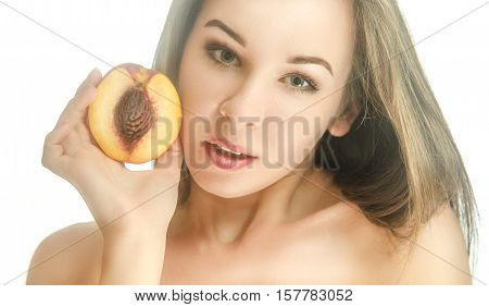 Beautiful girl with half of peach looking at the camera tilts his head to the side