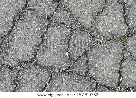 Closeup of damaged asphalt with many fissures