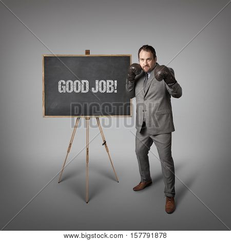 Good job text on  blackboard with businessman wearing boxing gloves