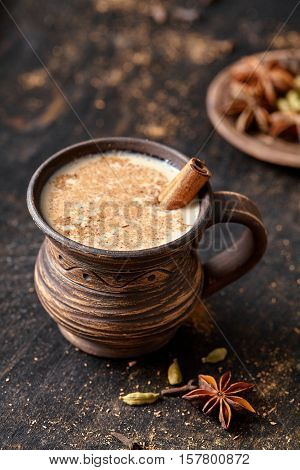 Masala pulled tea chai latte tasty hot Indian sweet milk spiced drink, ginger, fresh spices and herbs blend, anise organic infusion healthy wellness beverage teatime ceremony in rustic clay cup