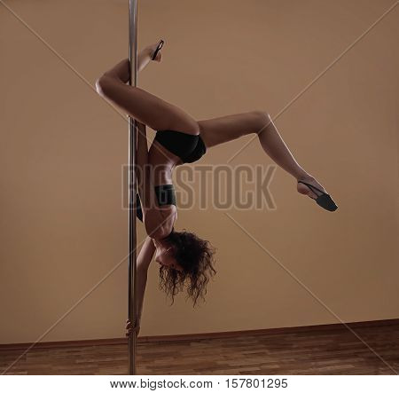 Young Sexy Woman Exercise Pole Dance On A Dark Background