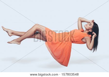Hovering beauty. Full length studio shot of attractive young woman in orange dress hovering in air and keeping eyes closed