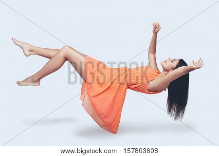 Flying so high. Full length studio shot of attractive young woman in orange dress hovering in air and keeping eyes closed