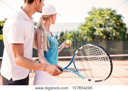Side view of tennis couple on court. are looking away