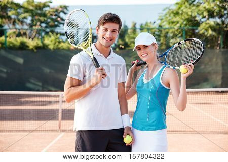 Happy tennis couple on court. looking at the camera. with rackets