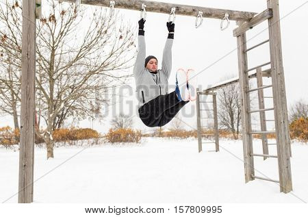 fitness, sport, exercising, training and people concept - young man doing leg pull ups on horizontal bar and flexing abdominal muscles outdoors in winter