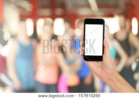 Female hand with smartphone against blurred group of people at gym
