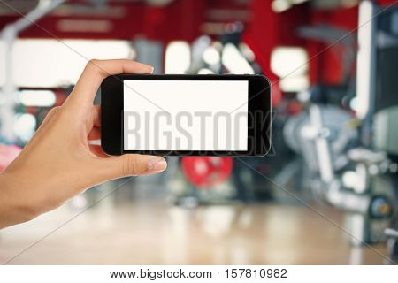 Female hand with smartphone against blurred gym interior background