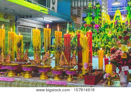 Bangkok, Thailand - December 22, 2015: Offerings to Buddha with flowers peacock feathers and candles in the alleys of Bangkok. Thai food for pay respect to god.