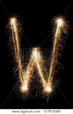 English big Letter W made from burning sparkles on black background. Shiny festive party firework font, latin alphabet text sign.