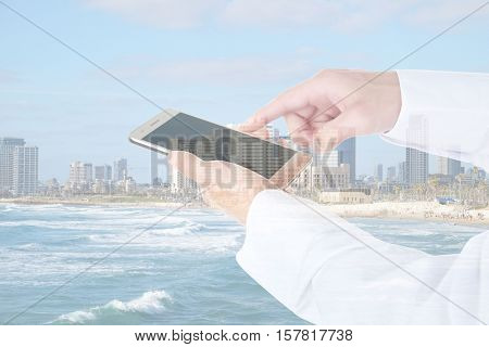 Double exposure of cityscape and male hands with smartphone.