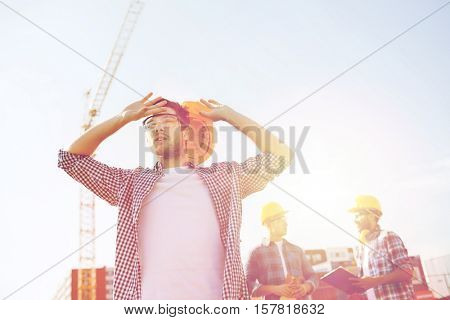 business, building, teamwork and people concept - group of builders in hardhats outdoors
