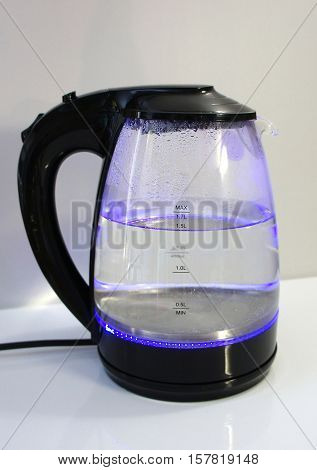 Glass electric kettle with water. Glass electric kettle with illuminated in the kitchen.