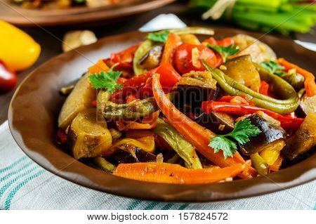 Vegetable stew (salad): bell pepper eggplant asparagus beans garlic carrot leek. Bright spicy aromatic dishes. Menu of Italian cuisine. Close up