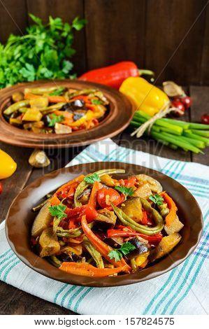 Vegetable stew (salad): bell pepper eggplant asparagus beans garlic carrot leek. Bright spicy aromatic dishes. Menu of Italian cuisine.