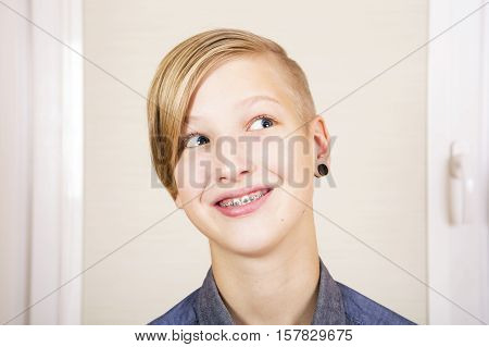 Teen with braces on his teeth and pierced ear. Orthodontics and bite correction.