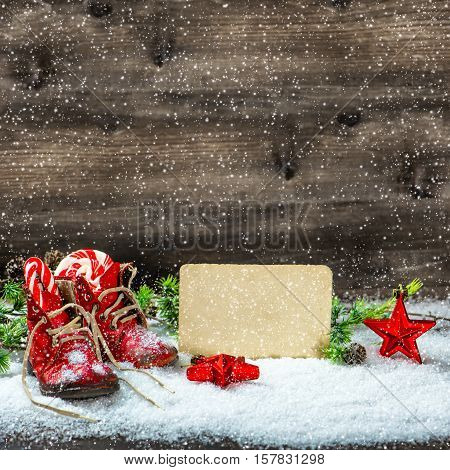 Christmas decoration red stars and vintage baby shoes. Falling snow effect