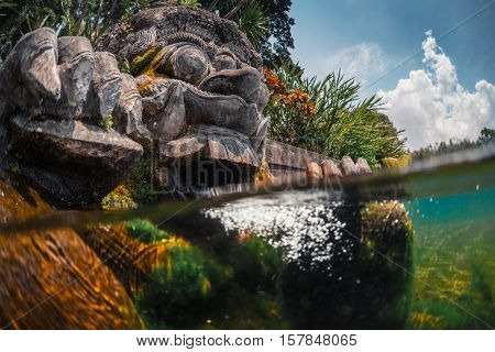 Underwater split shot of the stone sculpture in the Tirta Gangga water palace on the island of Bali