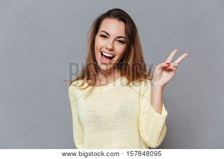 Portrait of a smiling happy woman showing victory sign and looking at camera isolated on the gray background