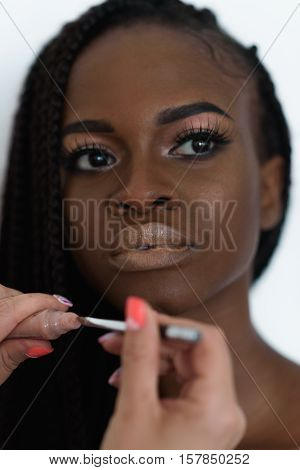 adorable, sexy, pretty photo model preparing to fashion shooting. Make up artist is taking a brown lipstick to her lips using a profesional brash.