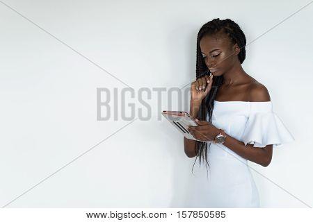 Sexy model with black skin is standing in front of a white wall and chatting in internet using her tablet. Girl is wearing white dress with bare shoulders and watch on her hand