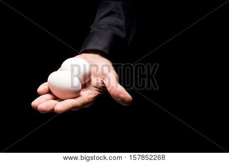 Natural product. Close up of young mans hand holding two eggs while demonstrating them and standing on black background.