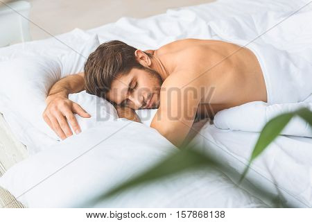 Serene young man is napping in bed. He is lying and relaxing