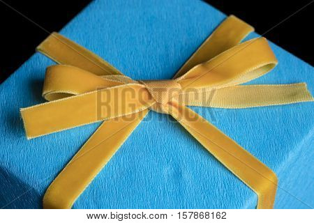 Closeup on yellow velvet ribbon bow tied on wrapped in turquoise textured paper gift on black background