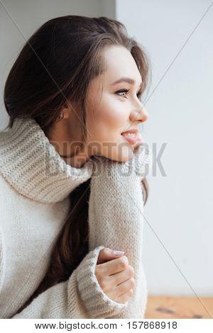 Side view of model in sweater. in studio. in profile. near the window.
