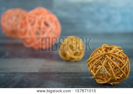 4 braided balls in yellow and orange on a wooden base