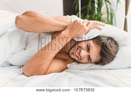 Man is lying on left side, screwing his eyes. He is covering ears by pillow beacause of noise