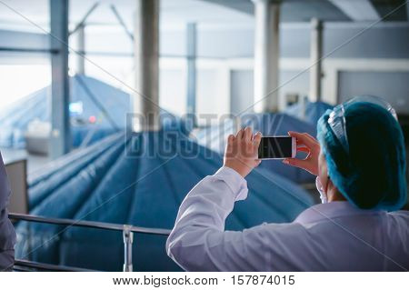 Woman In Overalls. An Employee In A White Robe Takes A Photo Shop Floor In The Brewery. On The Terri