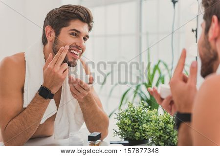 Happy young man is applying cream on his face after shaving. He is looking at mirror with satisfaction and laughing