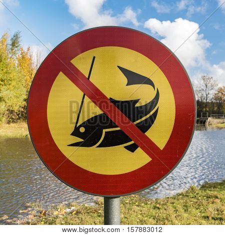 No fishing sign next to a park lake or pond.