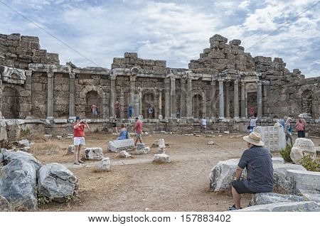 SIDE TURKEY - OCTOBER 02 2013: Tourists meandering through the ancient ruins of Side.