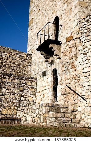 Stone medieval tower with portal and balcony