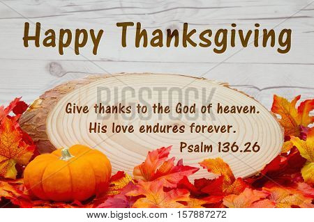 Happy Thanksgiving message Some fall leaves an alarm clock and wood plaque on weathered wood with text Psalm 136