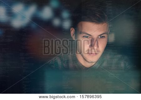 Young programmer coding at night in front of monitor
