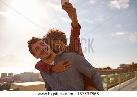 Laughing Piggy Backing Couple Taking Selfie