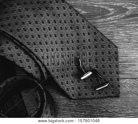 male tie and cufflinks in wooden background
