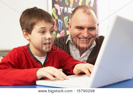 Schoolboy In IT Class Using Computer With Teacher